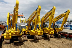 Pekerja mengatur sejumlah alat berat yang akan dikirim ke Sorong untuk kebutuhan tambang, di atas kapal pengangkutan, di Pelabuhan Paotere, Makassar, Sulsel, Sabtu (1/3). Himpunan Alat Berat Indonesia (Hinabi)  menargetkan produksi alat berat dalam negeri berkapasitas 10-30 ton digunakan untuk proyek konstruksi dan tambang pada tahun 2014 tumbuh 6% menjadi 6.500 unit dari tahun 2013 sebesar 6.127 unit. ANTARA FOTO/Ekho Ardiyanto/ss/pd/14